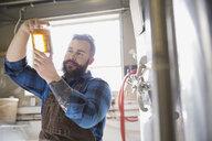 Brewery worker examining beer in beaker - HEROF06896