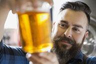 Close up brewery worker examining beer in beaker - HEROF06899