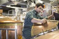 Brewery worker looking inside copper still - HEROF06941