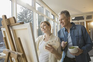 Couple painting at easel in living room - HEROF06986