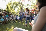 Neighbors enjoying egg and spoon race at summer neighborhood block party in park - HEROF07001