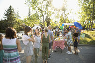 Neighbors standing in queue for buffet at summer neighborhood block party in park - HEROF07004