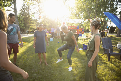 Neighbors playing with hacky sack at summer neighborhood block party in sunny park - HEROF07016
