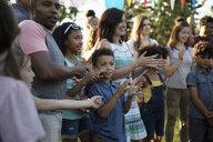 Neighbors clapping at summer neighborhood block party - HEROF07019
