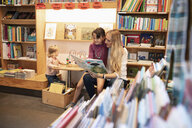 Mother and daughter reading book in bookstore - HEROF07025