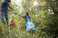 Mother and daughter volunteering, cleaning up garbage in park - HEROF07064