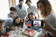 Man with camera phone photographing Latinx multi-generation family celebrating birthday with cake - HEROF07163