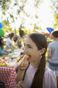 Girl eating hot dog at summer neighborhood block party in park - HEROF07202