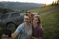Happy couple taking selfie with camera phone in front of SUV on mountain road, Alberta, Canada - HEROF07226
