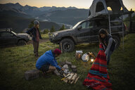 Friends camping, preparing campfire on remote mountain hilltop - HEROF07238