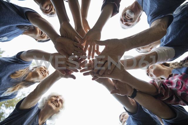 Happy volunteers joining hands in huddle - HEROF07244 - Hero Images/Westend61