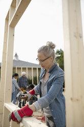 Female volunteer using hammer, helping build house - HEROF07256