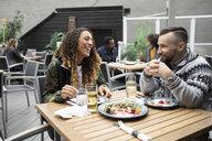 Happy couple enjoying lunch on cafe patio - HEROF07298