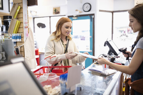 Female business owner helping customer at art supply shop counter - HEROF07310