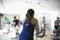 Female instructor on exercise bike leading spin class in gym - HEROF07370