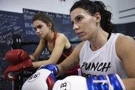 Focused, tough female boxers resting in gym - HEROF07373