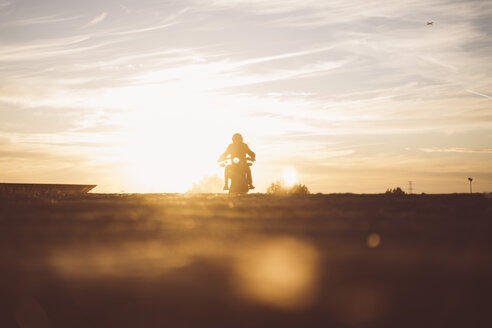 Silhouette of man riding custum motorcycle at sunset - OCMF00223