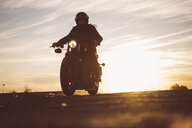Silhouette of man riding custum motorcycle at sunset - OCMF00226