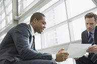 Businessmen discussing paperwork in office - HEROF07459