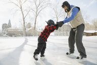 Father teaching son to ice-skate on outdoor rink - HEROF07462