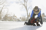 Father teaching son to ice-skate on outdoor rink - HEROF07468