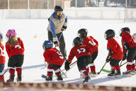 Coach instructing ice hockey team on rink - HEROF07534