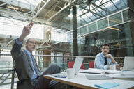 Businessman with arm raised in conference room meeting - HEROF07570