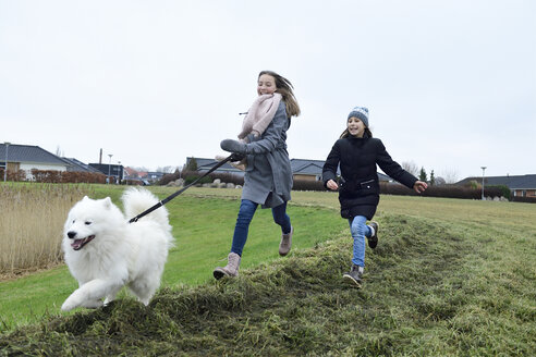 Two girls running on a meadow with dog having fun - ECPF00256