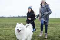 Two girls running on a meadow with dog having fun - ECPF00259