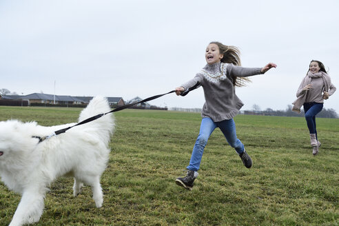 Two girls running on a meadow with  dog having fun - ECPF00262