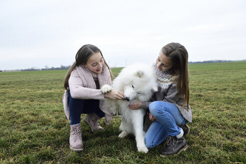 Two girls crouching on a meadow teaching dog - ECPF00265