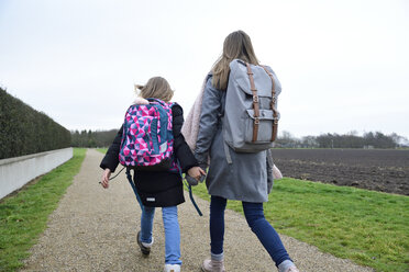 Back view of two sisters with backpacks walking hand in hand - ECPF00271