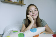 Portrait of smiling girl lying on bed - ECPF00274