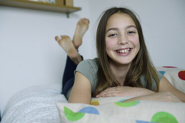 Portrait of laughing girl lying on bed - ECPF00277