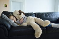 Girl relaxing on couch with oversized soft toy - ECPF00280