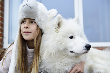 Portrait of content girl on terrace with her white dog - ECPF00286