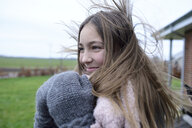 Portrait of smiling girl with blowing hair in winter - ECPF00292