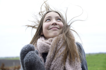 Portrait of smiling girl with blowing hair in winter looking up - ECPF00295