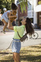 Happy mother lifting up daughter outdoors in the city - MAUF02397