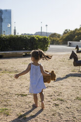 Rear view of little girl with teddy on a playground - MAUF02406