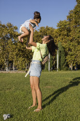 Happy mother playing with daughter in a park - MAUF02418