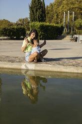 Happy mother with daughter at a pool in a park - MAUF02424