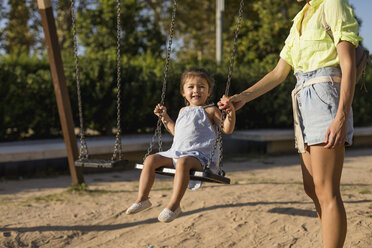 Mother holding daughter's hand swinging on a playground - MAUF02433