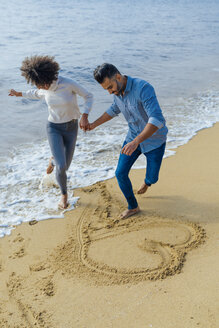 Spain, Barcelona, happy couple having fun on the beach drawing a heart in the sand - BOYF01278