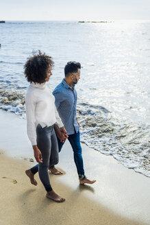 Spain, Barcelona, couple walking barefoot on the beach - BOYF01281