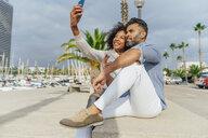Spain, Barcelona, happy couple taking a selfie at the marina - BOYF01299