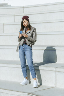 Spain, Andalusia, cadiz, Jerez, Young woman typing on mobile phone outdoors. - KIJF02209
