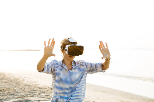 beautiful, blond, young woman is testing virtual 3D glasses, vr goggles on a wonderful beach in thailand, rayong - HMEF00183