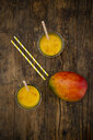 Mango and two glasses of Mango Lassi with curcuma and straws on wood - LVF07684
