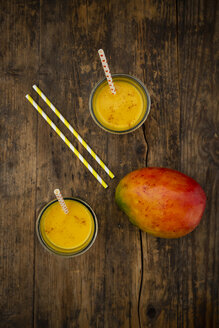 Mango and two glasses of Mango Lassi with curcuma and straws on wood - LVF07684